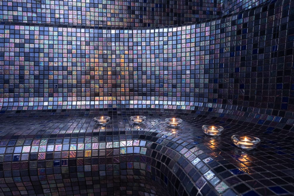 Photography of a tiled steam room with candles